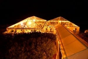40' x 60' and 40' x 40' clear top tents at night with chandeliers.