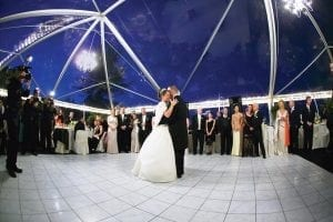 Wedding in a 40' x 60' tent featuring a clear top, chandeliers, and white dance floor.