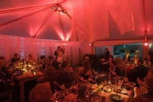 Wedding in a 30' x 40' frame tent featuring magenta color washing, pin spot lighting on the centerpieces, and custom sheer draping