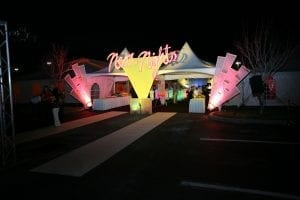 Neon Nights themed corporate event featuring twin 15'' x 15'' hi-peak entrance tents, custom signage and spandex panels.
