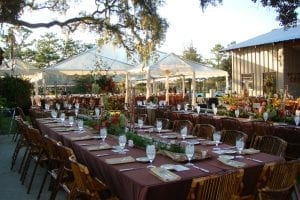Wedding on a private country estate featuring clear top tents installed on a custom built wood floor and bamboo chairs.