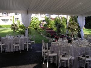 Fundraiser in a 40' x 100' frame tent featuring a custom built floor and stairs with black carpet, silver ballroom chairs, tent liner, and leg drapes.