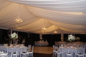 Medium silver chandeliers in a 40'' x 80'' frame tent with tent liner back lit with white lighting