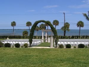 Wedding ceremony at a private waterfront estate featuring white wood chairs and sand arch.