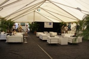 Inside view of a 40' x 100' frame tent with gable ends, window sidewalls, black carpet, and white leather furniture used at the 2010 Stuart boat show.