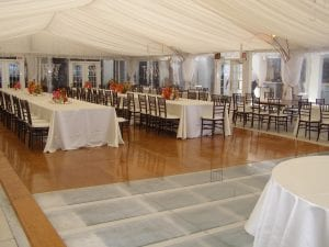 Wedding at a hotel featuring a combination wood and acrylic pool cover, 40' x 100' frame tent, tent liner, leg drapes, and clear sides.