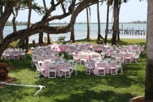 Wedding at a private waterfront home featuring white wood chairs and pink poly linens.