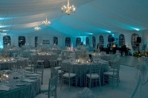 Black tie fundraiser held in a 50' x 90' frame tent featuring a tent liner back lit in blue, chandeliers, white carpet, and silver ballroom chairs.