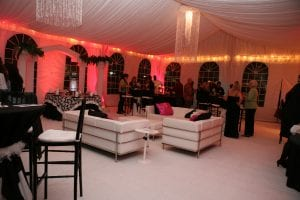 Décor perimeter lighting, custom chandeliers, and wall color wash in a 30'' x 50'' frame tent with tent liner.
