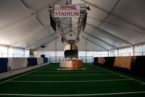 Super bowl party held in a 50' x 75' gable ended frame tent featuring multiple TV's mounted on trussing, a striped football field and a giant helmet.