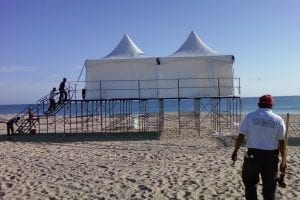 Staging set at 8'' high on beach with two 15'' x 15'' hi-peak tents on top.