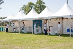 Hi-peak tents and white picket fence used for small carnival games at a recent corporate picnic.