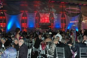 Black tie gala held in an airport hanger featuring color washed spandex panels, creative centerpieces, and silver ballroom chairs.
