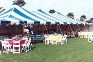 Blue and white striped 30' x 60' pole tent for a polo match with white sidewalls and white wood chairs.