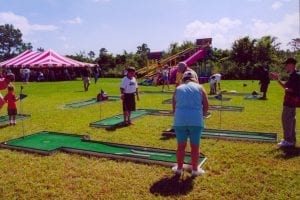 Miniature golf game at corporate picnic for 1,800 with cargo slide in the background.