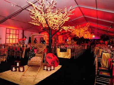 Black tie fundraiser held in a 20m x 50m clearspan tent featuring lighted cherry blossom trees, white wall drapes accented with lighted spandex panels, gold ballroom chairs, and kings tables.