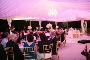 Wedding in a 40' x 60' frame tent featuring a color washed tent liner and crystal chandeliers.