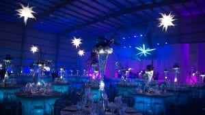 Black tie fundraiser held in an airplane hangar featuring lighted spandex tables and blue uplighting.