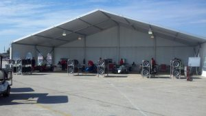 20m x 10m structure tent with an open end used for a temporary race garage.