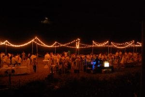Lobster and clam bake fundraiser on the beach featuring market lighting and a lighted bar.