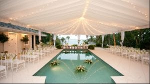 Wedding at a private waterfront home featuring a 40' x 60' frame tent with tent liner, leg drapes, and market lighting.