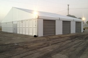 20m x 15m structure tent with custom made and installed roll up garagae doors and PVC hard walls.
