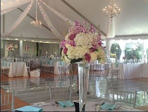 Wedding in a private home featuring a custom built wood and clear acrylic pool cover, 40' x 80' frame tent with sheer drape and market lighting.