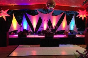 12' x 20' LED lighted frosted staging with spandex panels and mirror ball for New Year's Eve party.