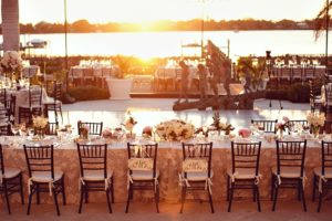 Wedding on the river in Vero Beach featuring a pool cover and mahogany chiavari chairs.