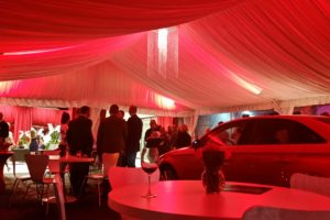 Grand opening for an auto delership featuring a tent liner colowashed in red with a custom chandelier.