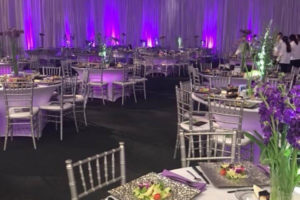 Annual gala in a large gym utilizing silver drape, uplighting, spandex linens and silver chiavari chairs.