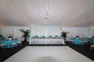 Wedding for 140 guests in a 40' x 80' frame tent featuring a tent liner, crstal chandelier, and gloss white dance floor.