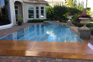 16' x 24' pool cover with a combination wood and acrylic deck at a private residence.