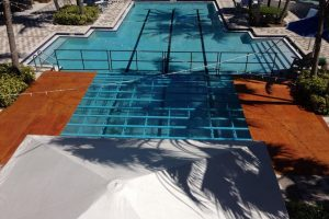 16' x 20' partial pool cover with a combination clear acrylic and wood deck with safety railing at a country club.